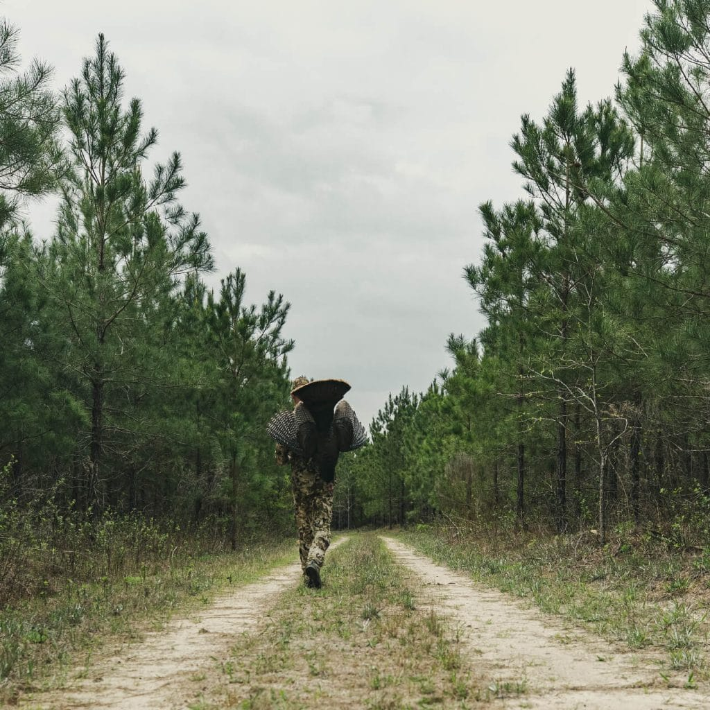 Man dressed in camo carrying a turkey down a path