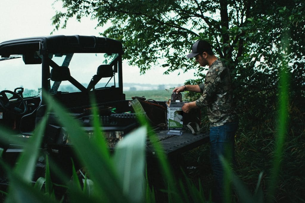 Man pulling out a Delta Cellular Trail Camera from box in back of ATV