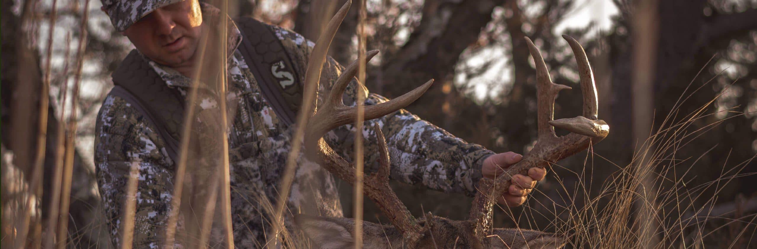 Man dressed in camo holding deer antlers