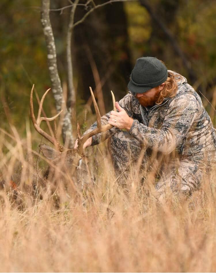 Man dressed in camo tagging deer antlers