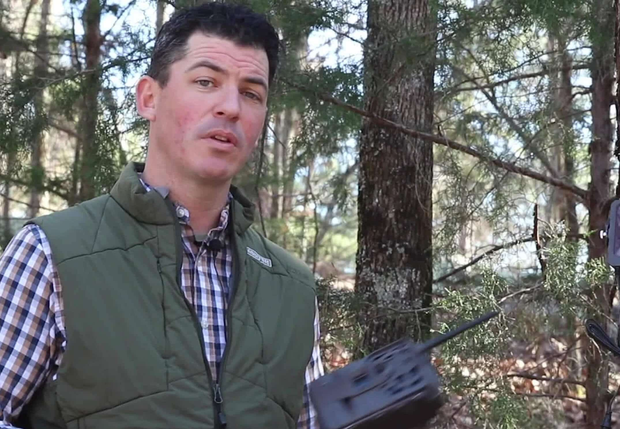 Man standing in woods holding a cellular trail camera