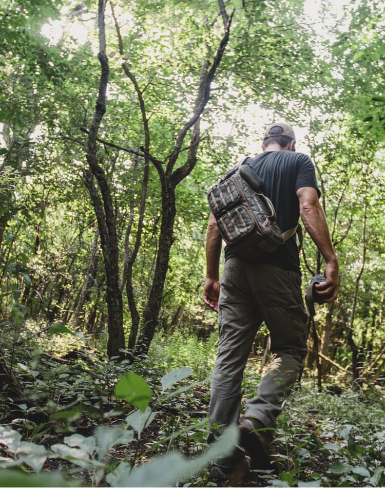 Man with camo trail camera carrier on his back walking through the woods