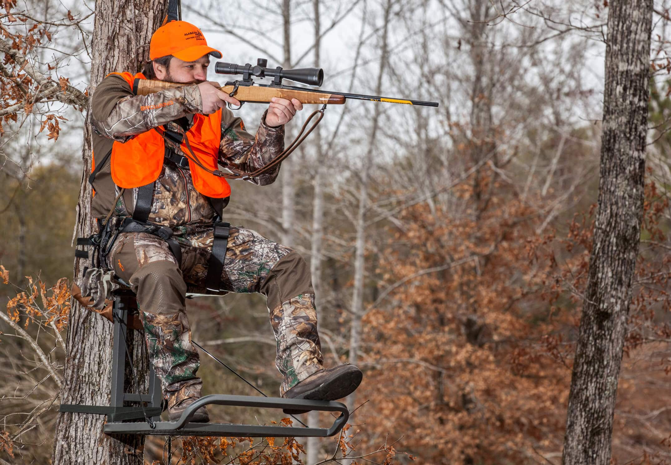 Man dressed in camo in a tree stand aiming his gun