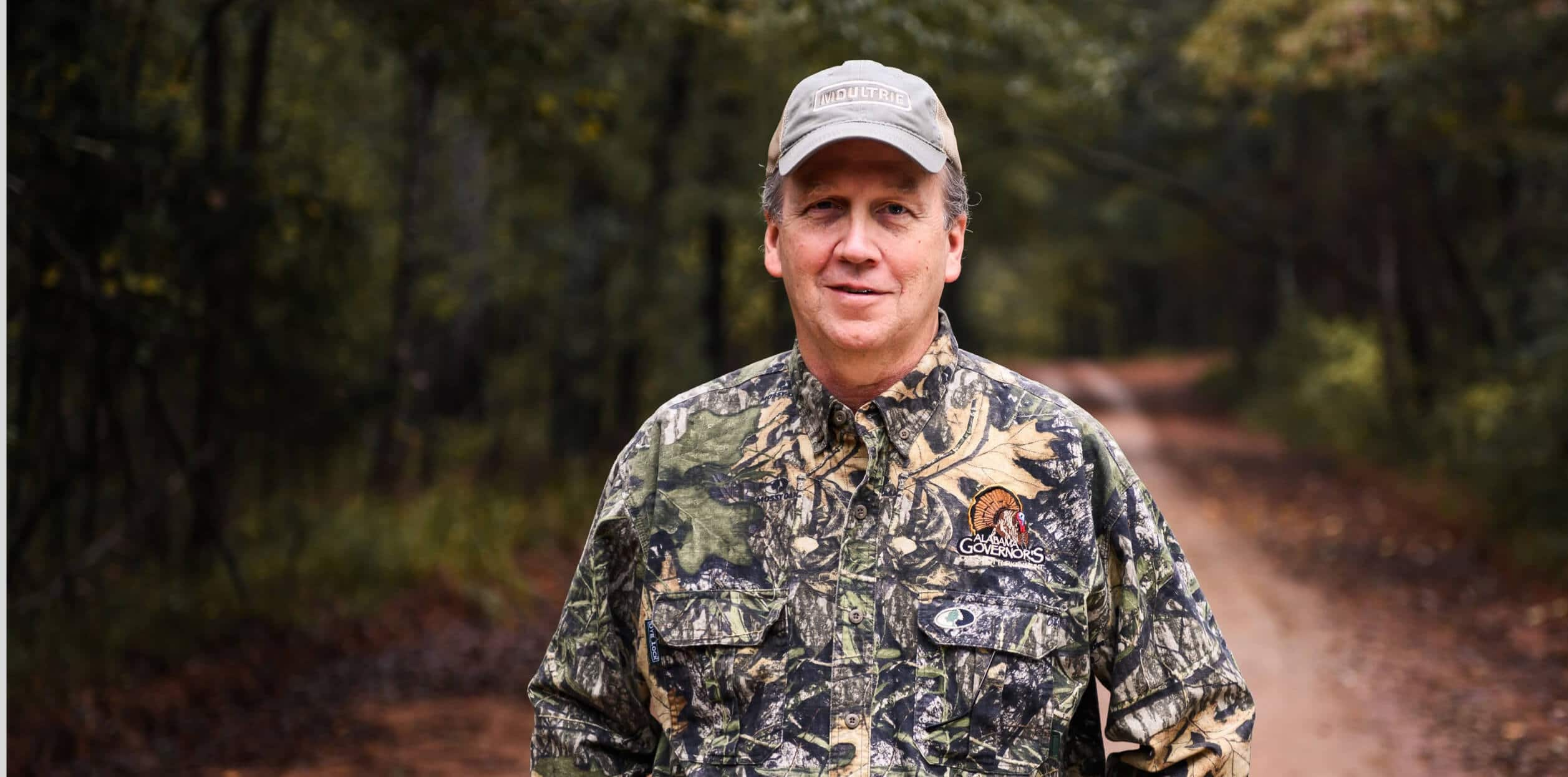 Man dressed in camo standing on a trail in the woods